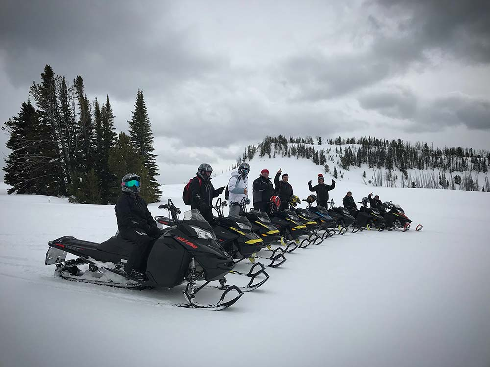 line of snowmobilers trail riding in montana