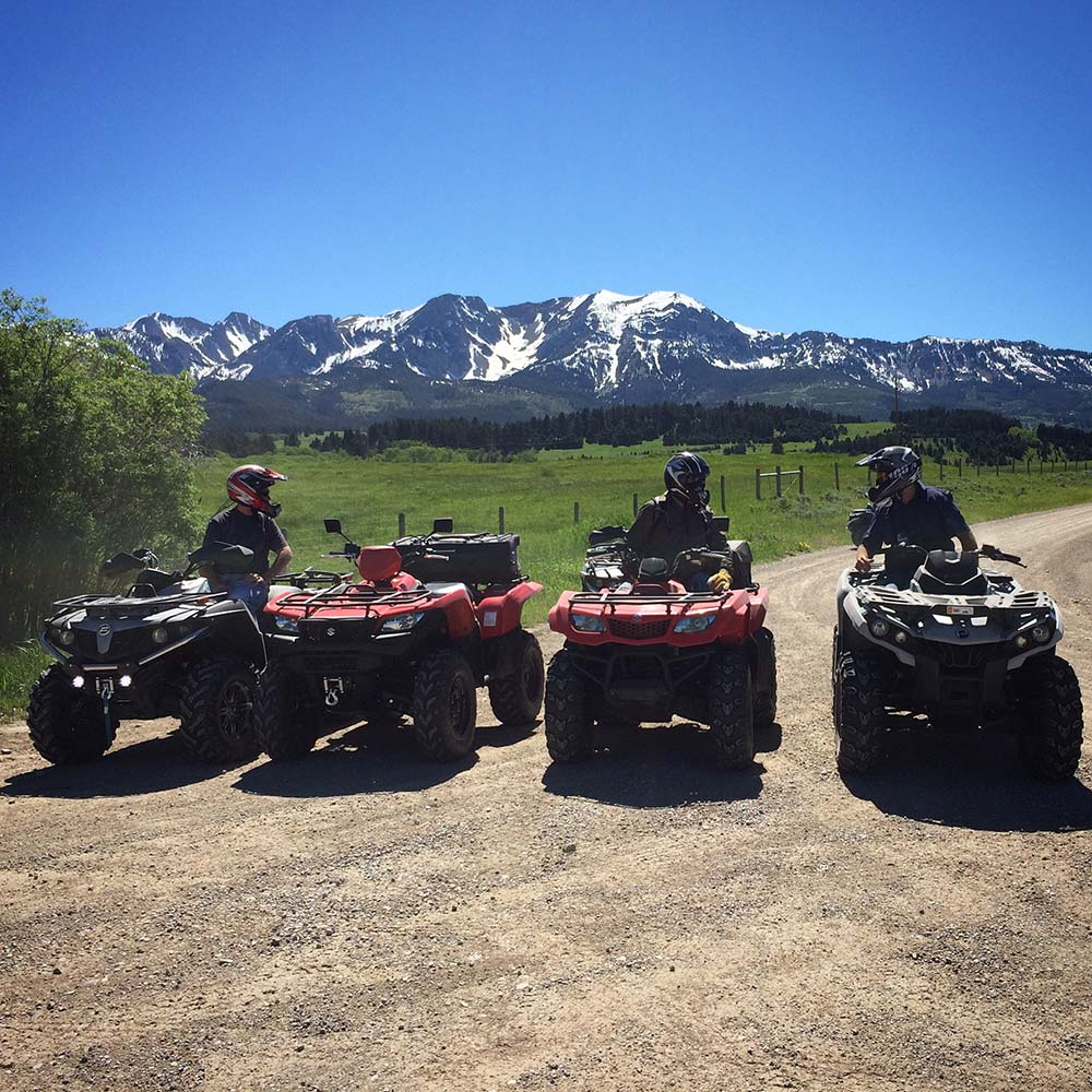 atv riders trail riding in montana with mountains in background